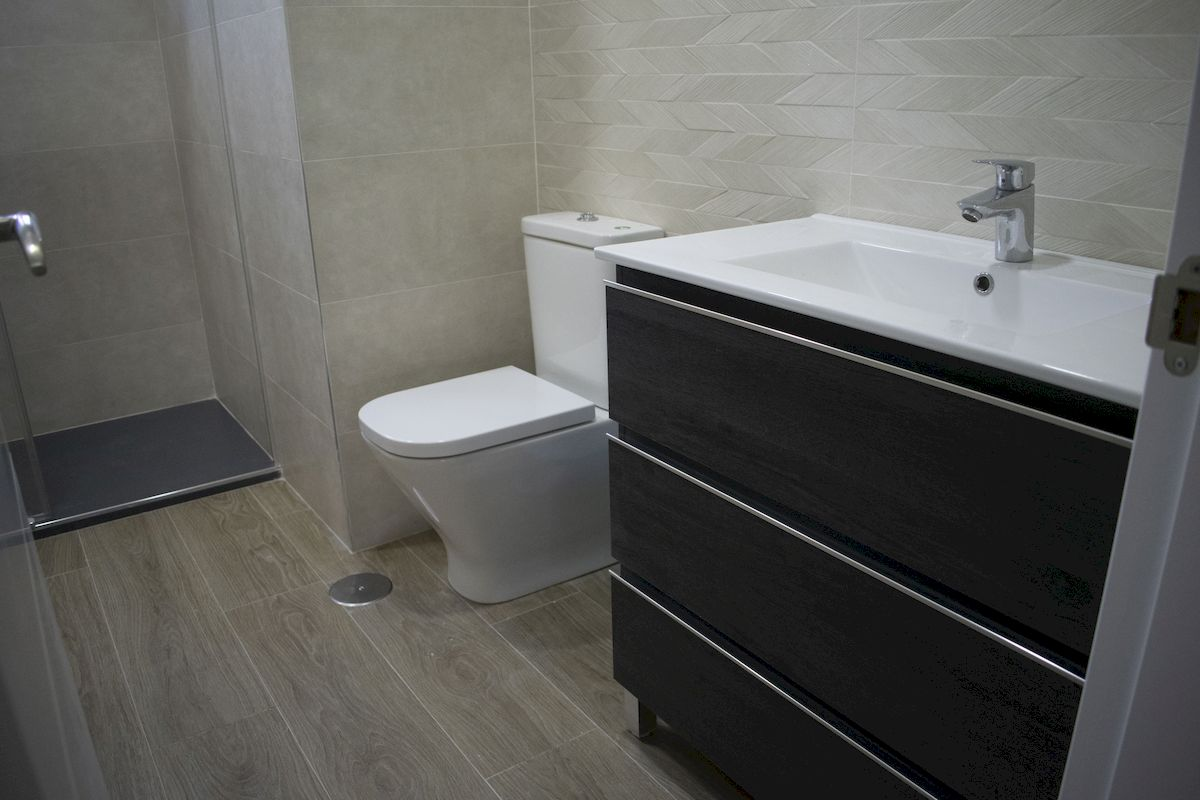 Detalle plato de ducha, inodoro compacto de baño mueble de lavabo